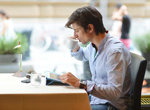 Man reviewing reports with coffee